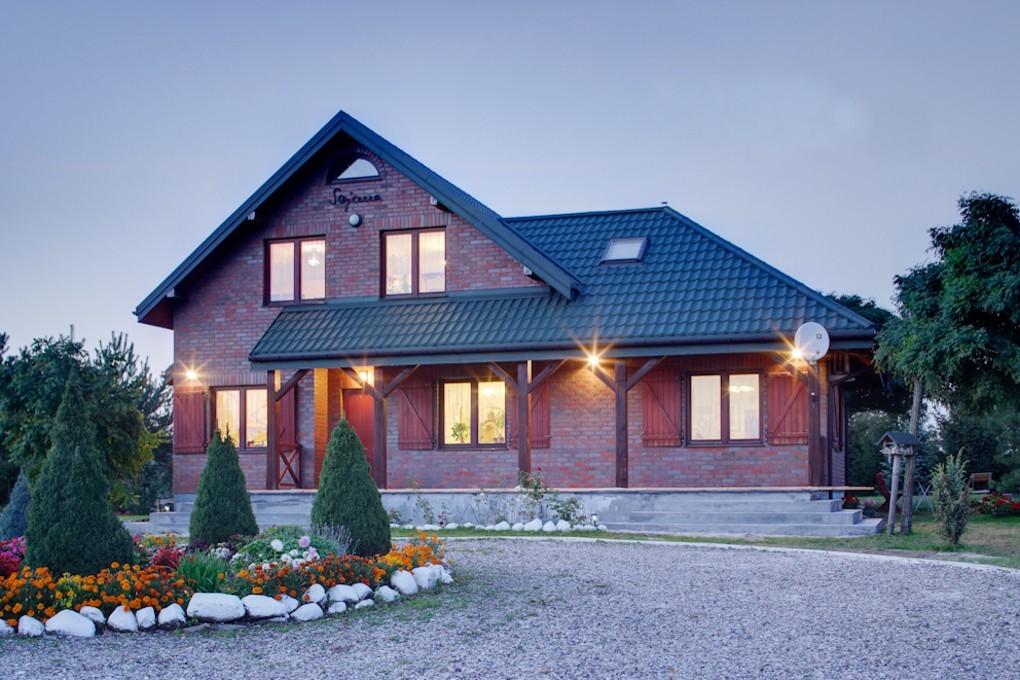 Pfannenblech Szafir®auf Klinkerhaus mit Satteldach in Dämmerung - Farbe RAL6005 Moosgrün - als Referenz - Longhouse GmbH