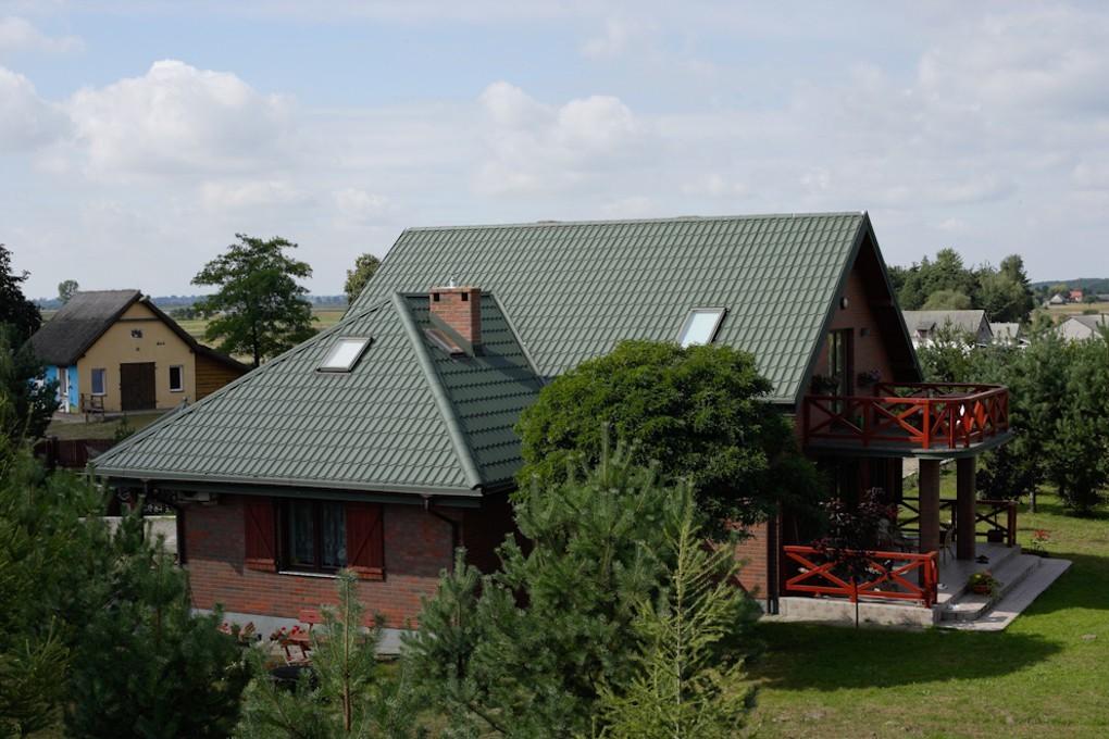 Pfannenblech Szafir®auf Klinkerhaus mit Satteldach und Anbau mit Walmdach - Farbe RAL6005 Moosgrün - als Referenz - Longhouse GmbH
